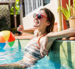 Woman leaning on edge of in-ground pool - Our Pools section | Pool and Spa Superstore Inc.