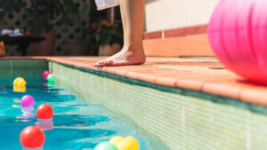Girl standing by swimming pool   Owner resources   Pool and Spa Superstore Inc.