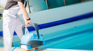 Man with robotic pool cleaner equipment cleaning swimming pool | Pool Supplies & Equipment | Pool and Spa Superstore Inc.